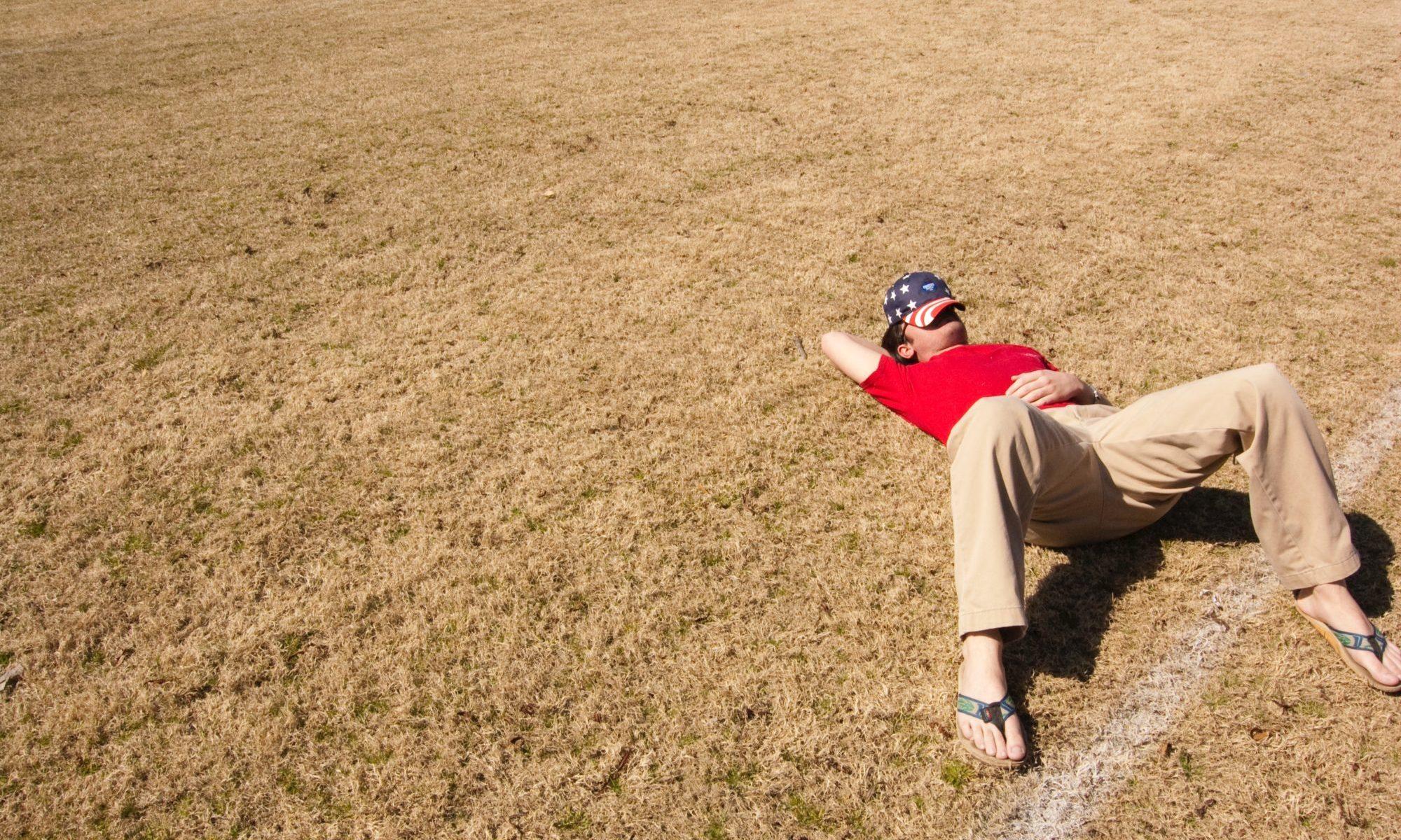 芝生で寝る男