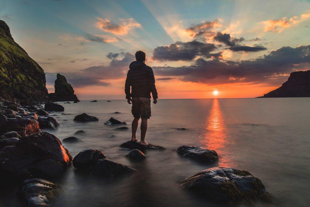 夕日を見て立つ男