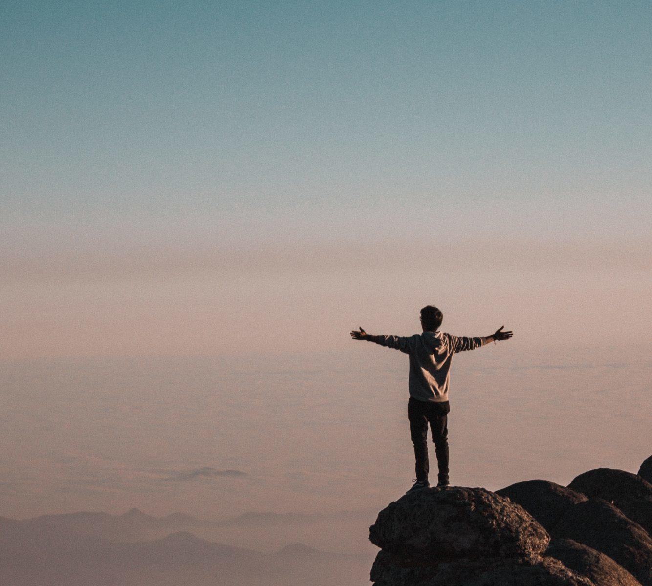 山の頂上から雲を眺める男