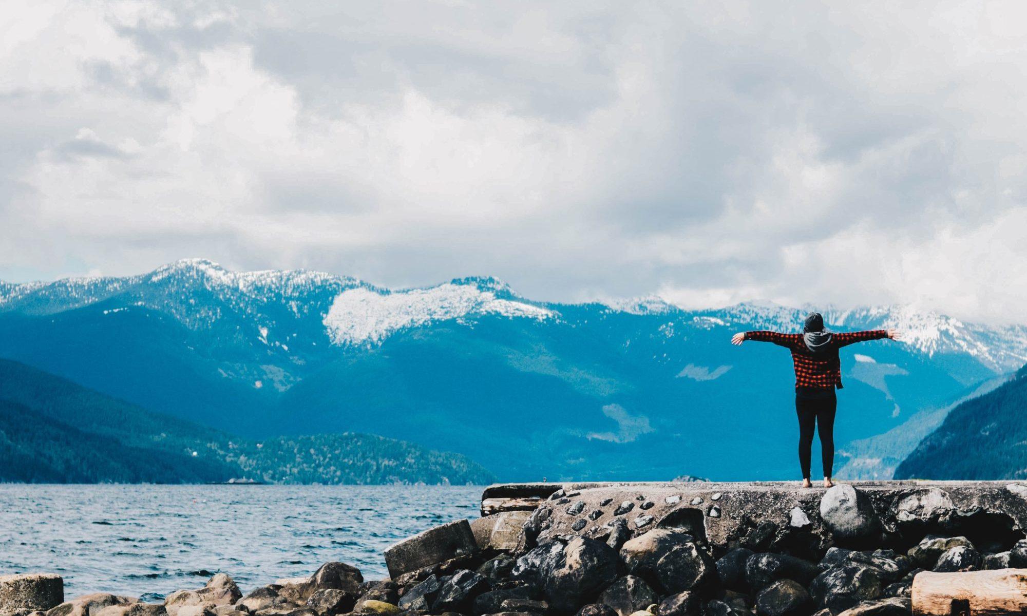 水と山脈の近くに腕を広げる人